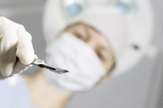 Perspective of a patient on a operating table who sees the doctor above him with a scalpel in his hand. Focus only on the scalpel.